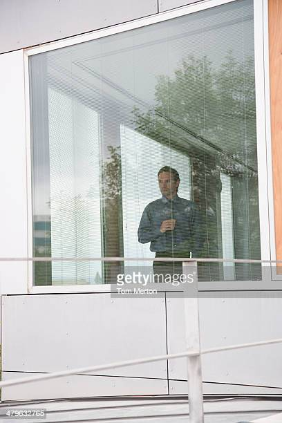businessman staring out office window with coffee - lingering stock pictures, royalty-free photos & images