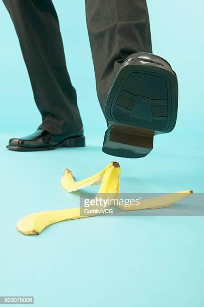 businessman stepping on banana peel - casca de banana - fotografias e filmes do acervo