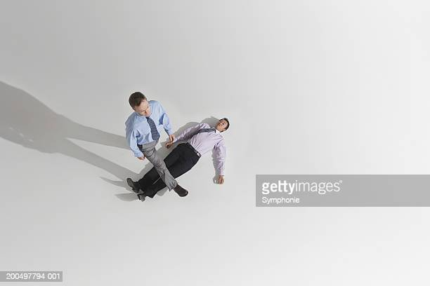 Businessman stepping over colleague lying on ground, elevated view