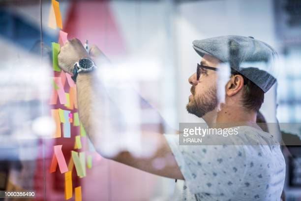 Businessman sticking adhesive note on glass