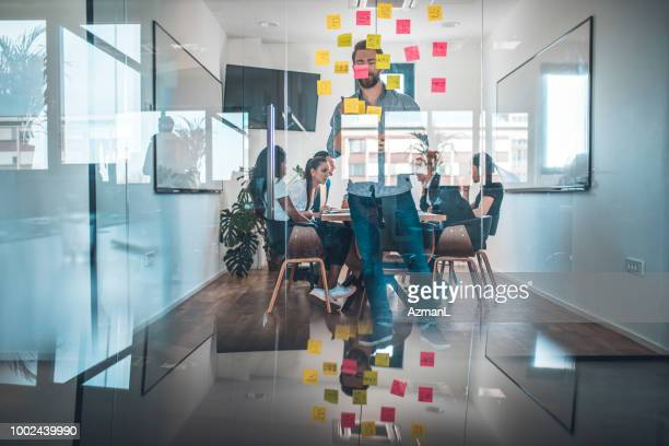 Businessman sticking adhesive note on glass wall