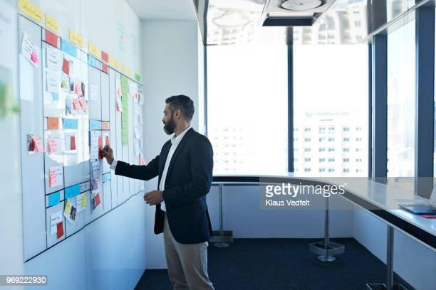 businessman sticking note on whiteboard in office - labeling - fotografias e filmes do acervo