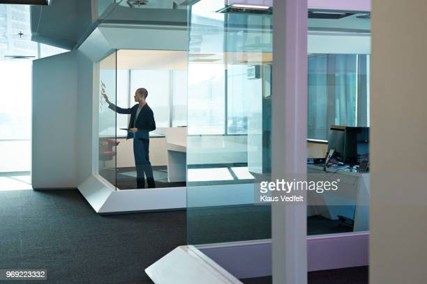 Businessman sticking notes on glass wall inside high-end corner office