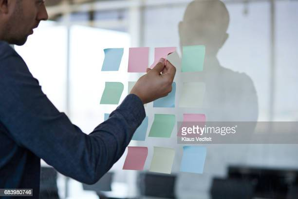 businessman sticking paper note on glass wall - strip stock pictures, royalty-free photos & images