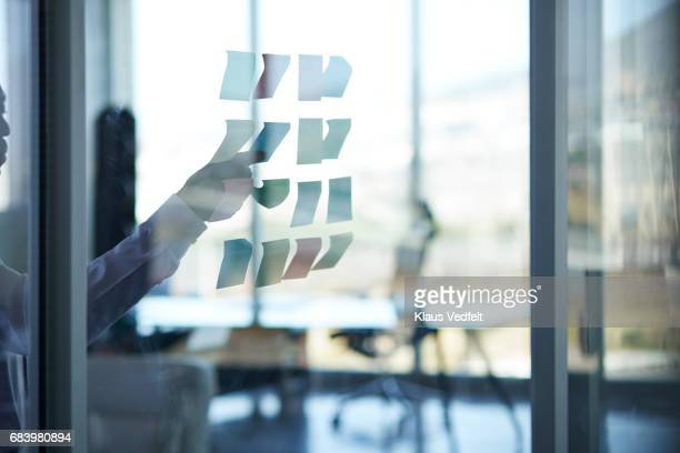 businessman sticking paper note on glass wall - soft focus stock pictures, royalty-free photos & images