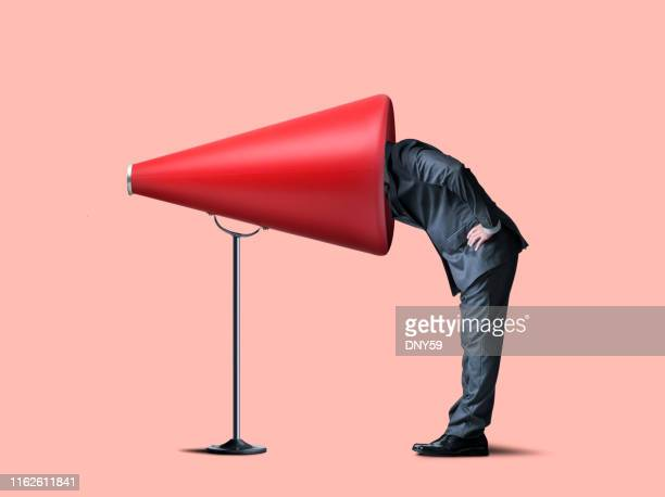 businessman sticks head into large red megaphone - communication problems stock pictures, royalty-free photos & images