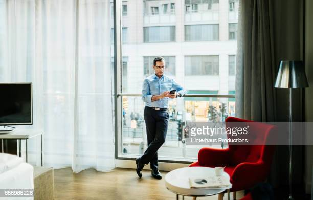 Businessman Stood In Hotel Room Using His Phone