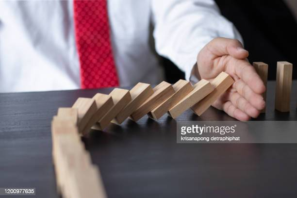 businessman stop domino effect. risk management and insurance concept - inconvenience stock pictures, royalty-free photos & images