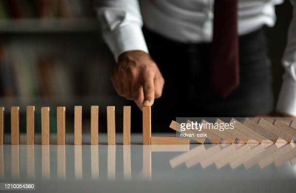 businessman stop domino effect. risk management and insurance concept - risk stock pictures, royalty-free photos & images