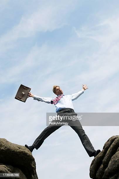 Homme d'affaires qui enjambe la vallée entre deux Rocks