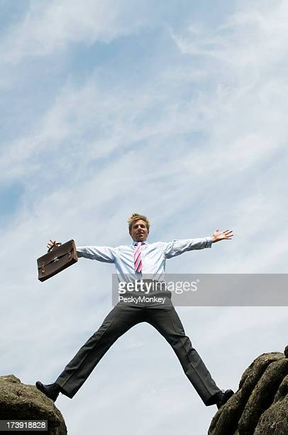 Businessman Straddles the Gap between Rocks