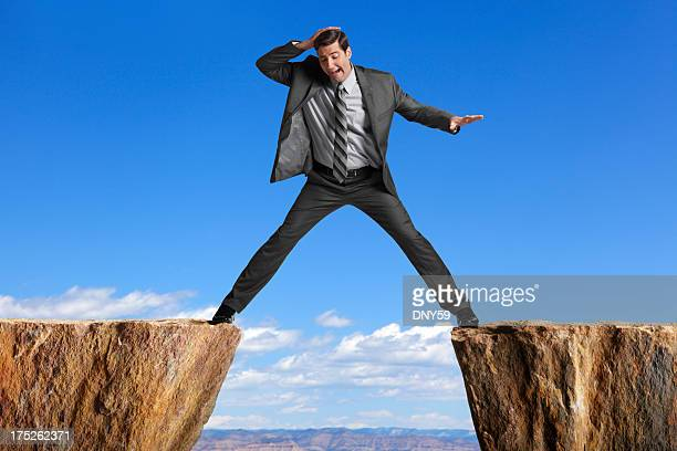businessman straddling the divide created by two cliffs - benen gespreid stockfoto's en -beelden