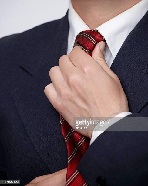 Businessman straightening his necktie knot