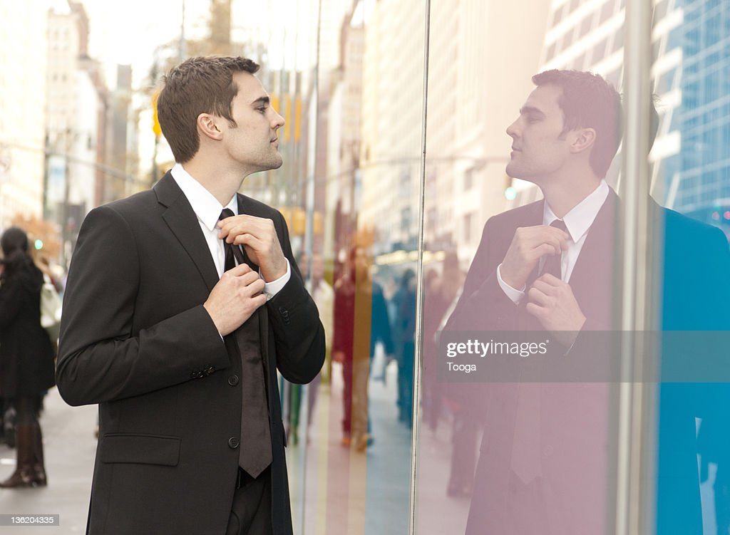 Businessman straightening his tie in reflection : Stock Photo