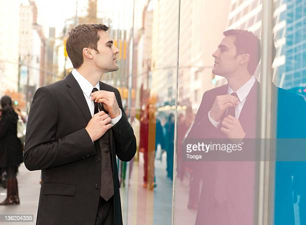 Businessman straightening his tie in reflection