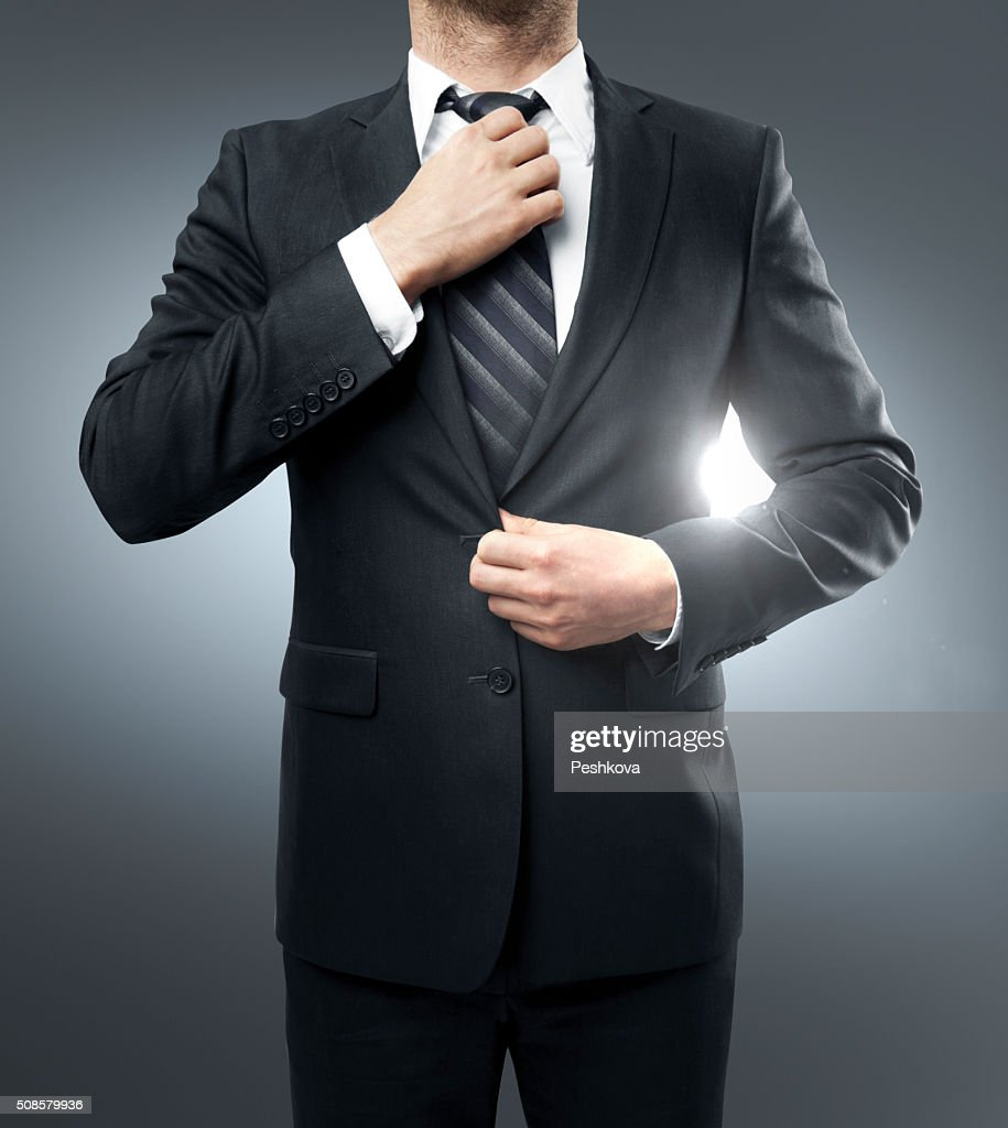 Businessman straightens his tie : Stock Photo