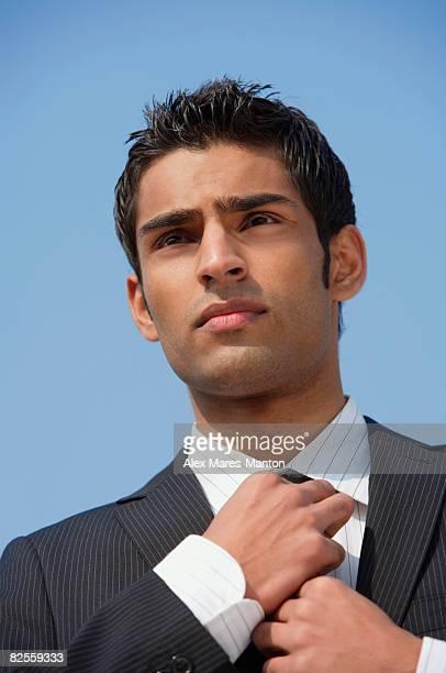 businessman straightens his tie