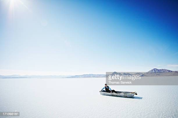 Businessman stranded in small boat without oars
