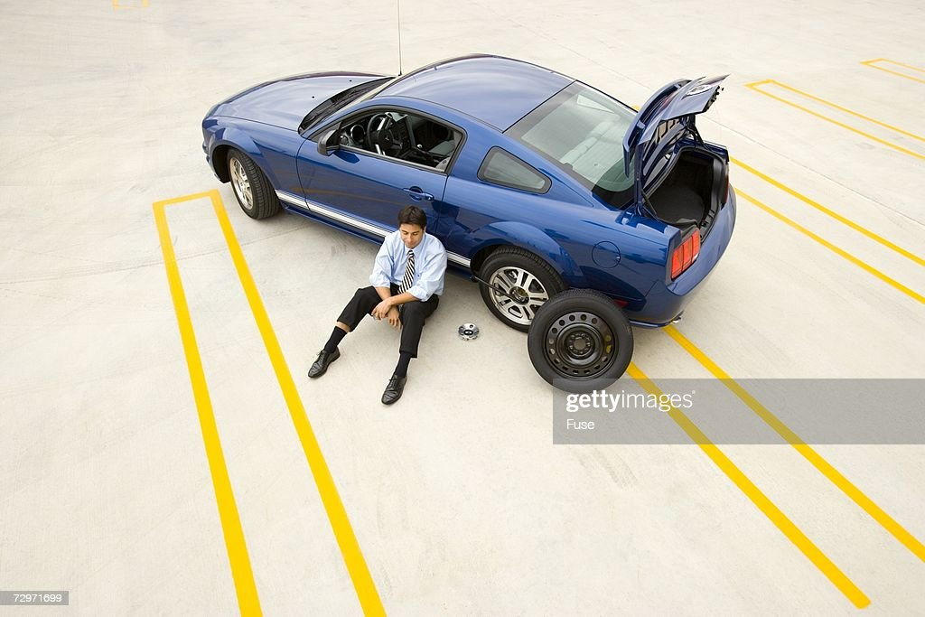 Businessman stranded with a flat tire : Stock-Foto