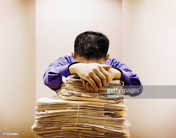 Businessman stressing with stack of documents.