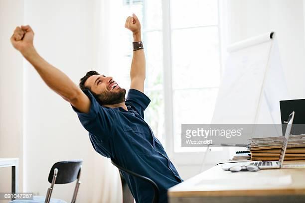 businessman stretching at desk - éxito fotografías e imágenes de stock
