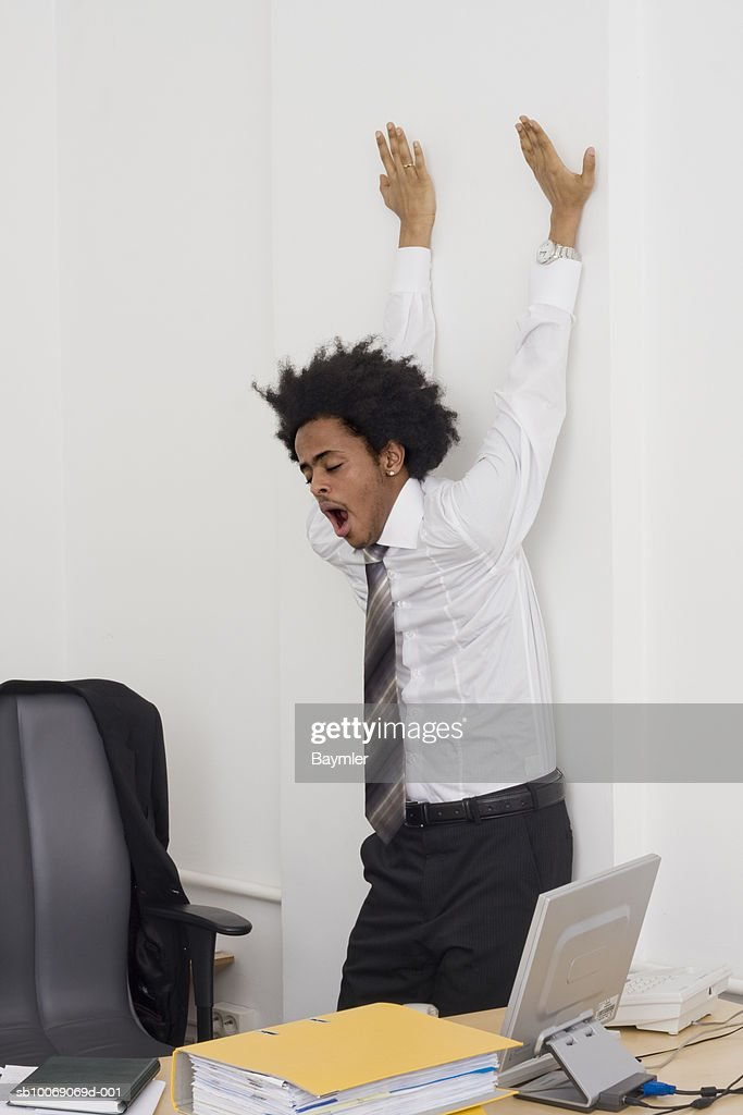 Businessman stretching in office (Digital Composite) : Stockfoto