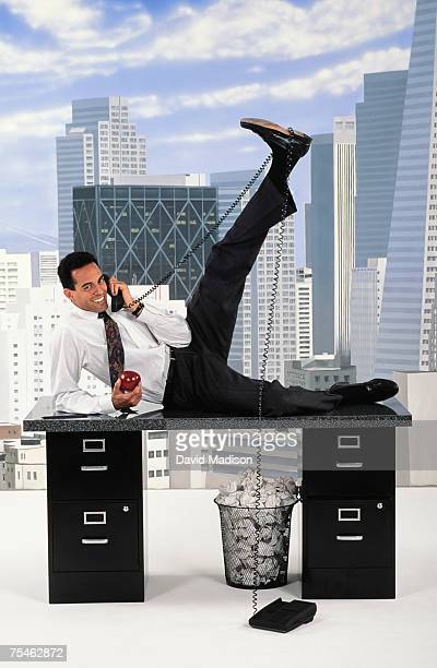 Businessman stretching on desk while talking on the telephone in office, against false backdrop of San Francisco cityscape.