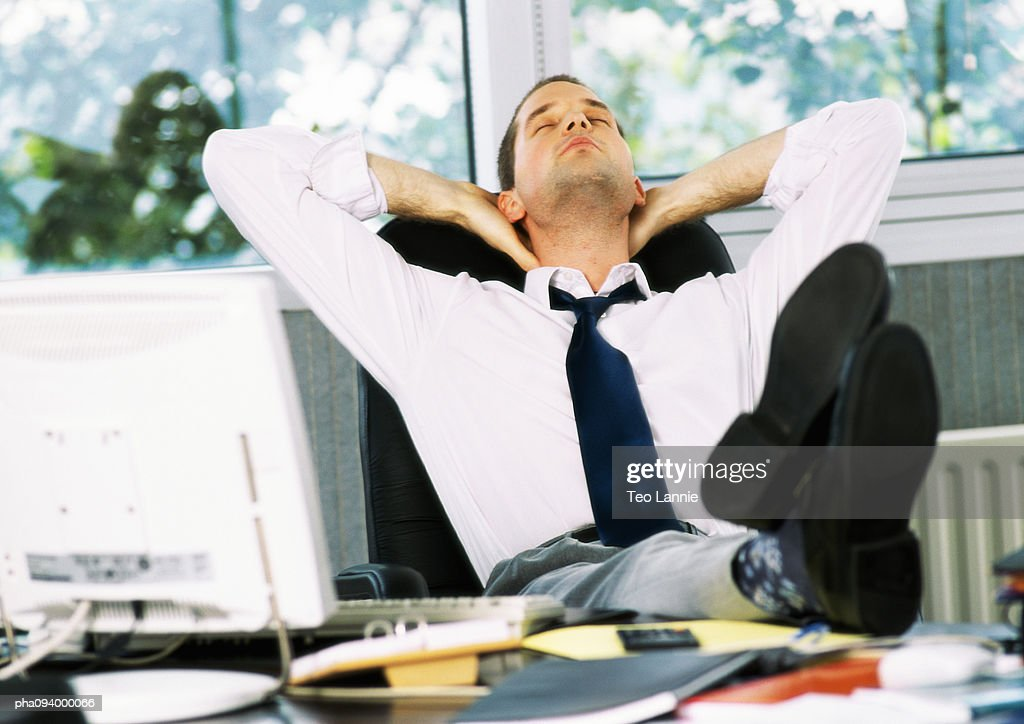 Businessman stretching with feet on desk : Stockfoto