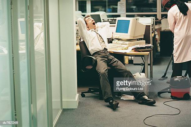 Businessman Stretching, Yawning and Working Late in the Office
