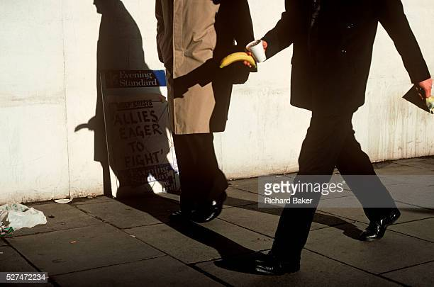 A businessman strides along a London street holding a banana whose shadow appears to be part of another man's anatomy As strong sunlight shines on...