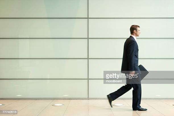 Businessman Striding Down Office Corridor
