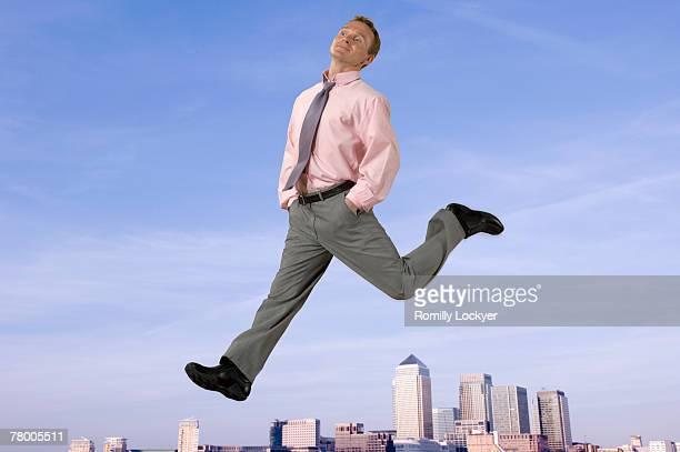 Businessman striding over city skyline