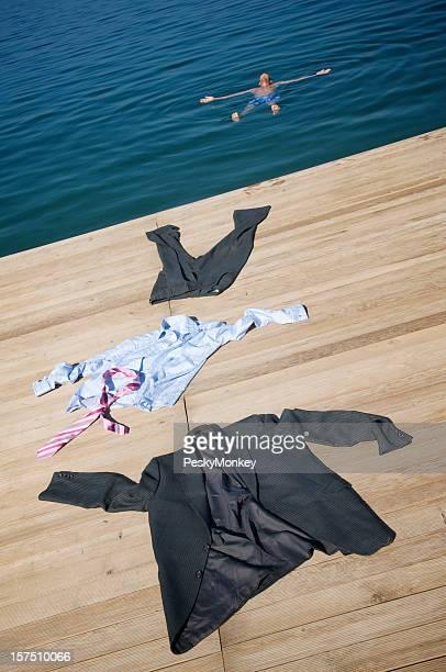 ビジネスマンストリップオフのスーツで水とフロート
