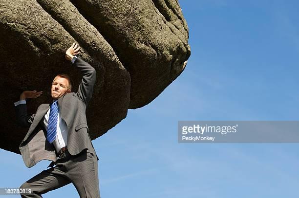 Businessman Struggles Heaving Massive Rock Boulder into the Sky
