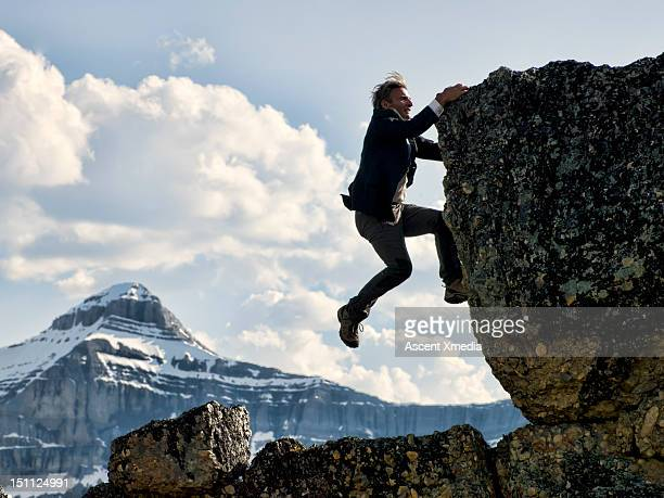 Businessman struggles to climb summit.