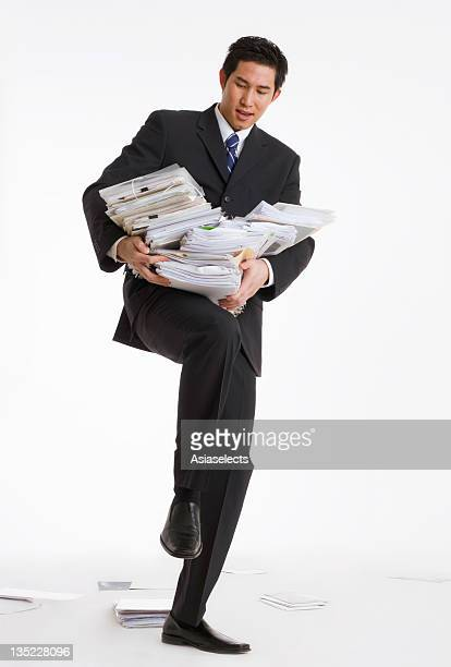 Businessman struggling to carry a stack of files