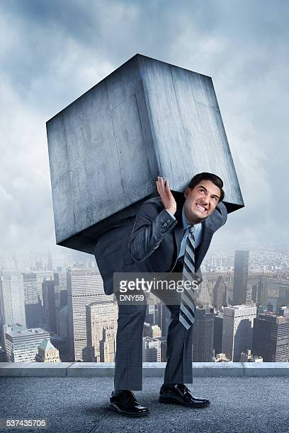 businessman struggling under weight of concrete block - bending over stock pictures, royalty-free photos & images