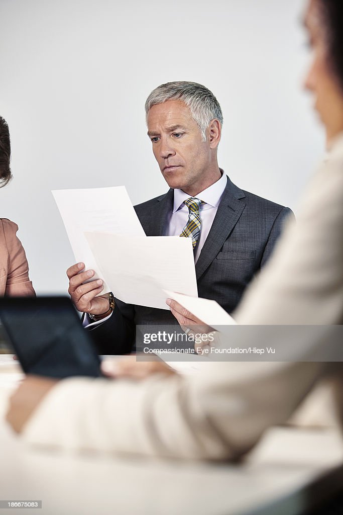 Businessman studying document in meeting room : Stock Photo