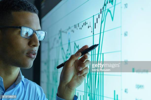 businessman studying graphs on an interactive screen in business meeting, close up - big data stock pictures, royalty-free photos & images