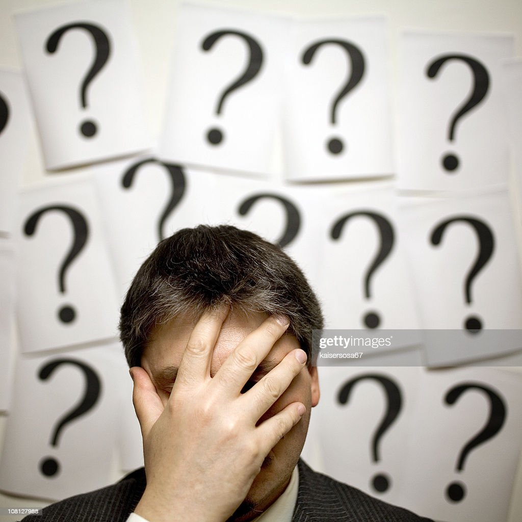 Businessman Surrounded by Question Marks : Stock Photo