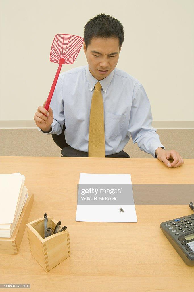 Businessman swatting fly on desk : Stock Photo