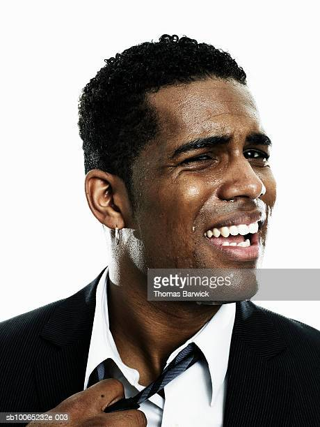 businessman sweating, pulling at tie, close-up - uncomfortable stock pictures, royalty-free photos & images