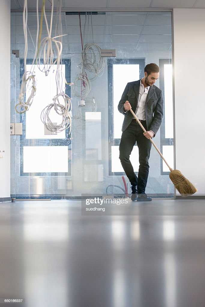 Businessman sweeping new office floor : Stock Photo