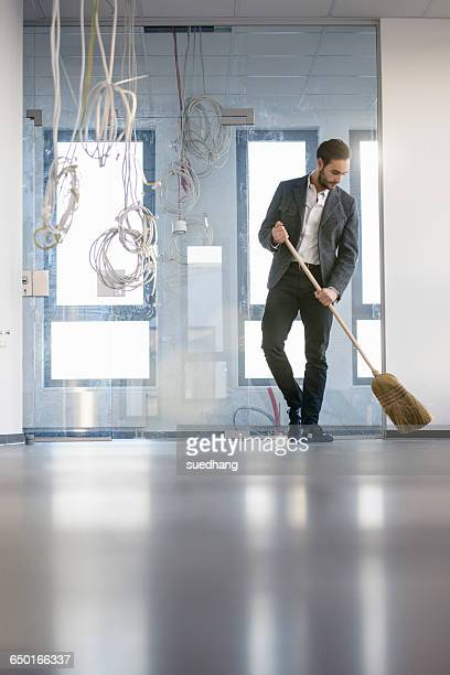 Businessman sweeping new office floor