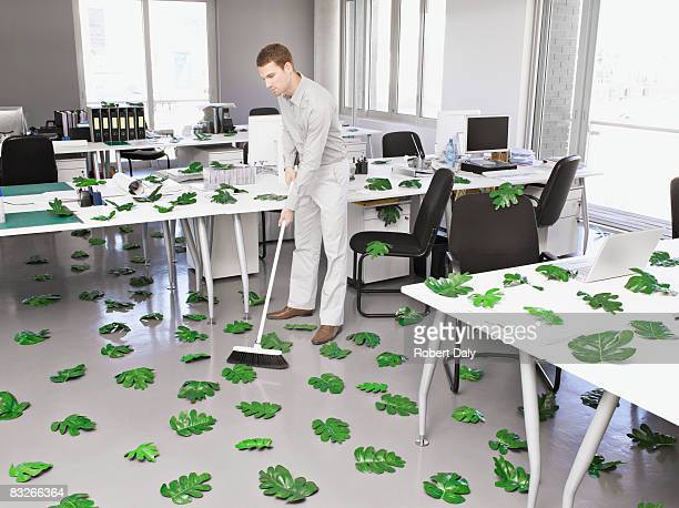 Businessman sweeping up green leaves in office