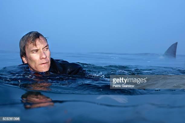 Businessman Swimming near Shark