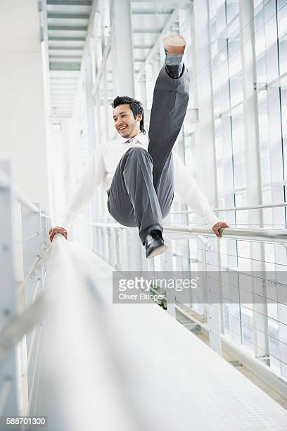 businessman swinging from railings - oliver eltinger stock-fotos und bilder