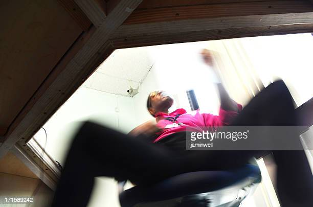 businessman swinging in chair perusing document - chairperson stock pictures, royalty-free photos & images