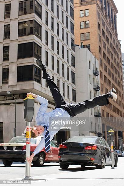 Businessman swinging on parking meter