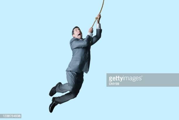 ロープでスイングビジネスマン - もがく ストックフォトと画像